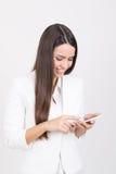 Tragendes Weiß der glücklichen Geschäftsfrau unter Verwendung des Smartphone Stockfotos