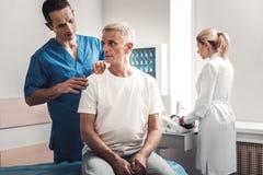 Tragendes weißes Hemd des besorgten Mannes, das auf Bett im medizinischen Raum sitzt lizenzfreie stockfotografie