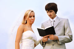 Tragendes weißes Kleid des Bräutigams und der Braut las Bibel stockfotos
