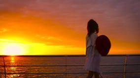 Tragendes weißes Kleid und Hut der jungen attraktiven Frau, die auf Seehintergrund bei erstaunlichem Sonnenuntergang aufwerfen stock video