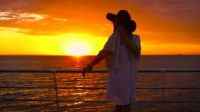 Tragendes weißes Kleid und Hut der jungen attraktiven Frau, die auf Seehintergrund bei erstaunlichem Sonnenuntergang aufwerfen stock footage