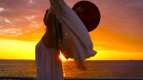 Tragendes weißes Kleid und Hut der jungen attraktiven Frau, die auf Seehintergrund bei erstaunlichem Sonnenuntergang aufwerfen stock video footage