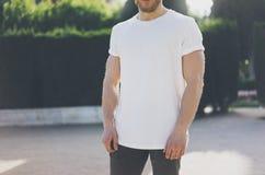 Tragendes weißes leeres T-Shirt des Foto-bärtigen muskulösen Mannes Grüner Garten-Hintergrund im Freien verwischt horizontales Mo Stockbilder