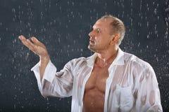 Tragendes weißes nasses Hemd des Bodybuilders steht im Regen Stockbilder