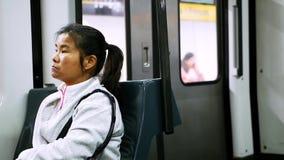 Tragendes weißes sportives Hemd der Asiatin sitzt in beweglichem Zug und schaut herum stock footage