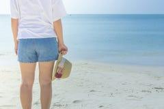 Tragendes weißes T-Shirt der Frau, sie stehend auf Sandstrand und Webarthut in der Hand halten, sie das Meer und den blauen Himme stockbild