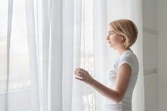 Tragendes weißes T-Shirt der jungen Frau, das heraus durch Fenster schaut Lizenzfreie Stockbilder