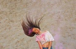 Tragendes weißes T-Shirt des attraktiven brunette Mädchens, das Holi-Farbfestival an der Wüste feiert lizenzfreies stockbild