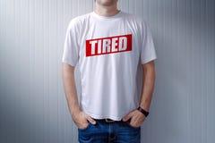 Tragendes weißes T-Shirt des Kerls mit Aufkleber ermüdete gedruckt auf Kasten stockfotografie