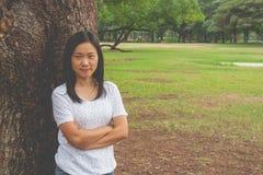 Tragendes weißes T-Shirt, sie stehend auf grünem Gras und Lächeln der Frau lizenzfreie stockfotos