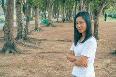 Tragendes weißes T-Shirt, sie stehend auf grünem Gras und Lächeln der Frau stockbild