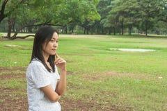 Tragendes weißes T-Shirt und Stellung der Frau auf grünem Gras, sie etwas denkend lizenzfreies stockfoto