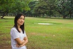 Tragendes weißes T-Shirt und Stellung der Frau auf grünem Gras, sie etwas denkend stockbilder