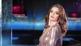 Tragendes Zauberkleid der schönen Modefrau mit dem Funkeln, das in den Lichtern und im Aufflackernhintergrund aufwirft stock footage
