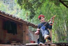 Tragendes Zhuang Kleidungsmädchen, welches das guqin spielt Stockfotografie