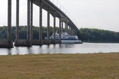 Traghetto che passa al di sotto di un ponte fotografia stock
