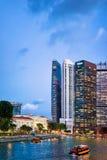 Traghetto e grattacieli del centro finanziario a Singapore alla notte Fotografia Stock