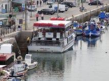 Traghetto e pescherecci attraccati sul fiume fotografia stock