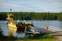 Traghetto giallo del cavo attraverso il canale di Kutvele sul lago Saimaa, Finlandia immagine stock