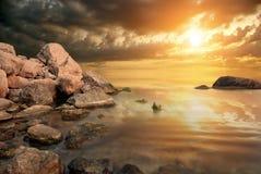 Tragisk solnedgång på bakgrund av havsklippor Fotografering för Bildbyråer