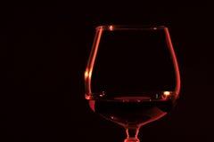 Trago de brandy en luz de una vela Foto de archivo