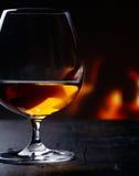 Trago de brandy que se calienta antes de un fuego que brilla intensamente Imágenes de archivo libres de regalías
