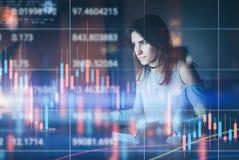 Traider della giovane donna che lavora all'ufficio moderno di notte Grafico tecnico di prezzi e grafico rosso e verde dell'indica immagine stock