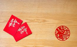 Traidtional Chinese red pockets and paper cut on table Royalty Free Stock Image