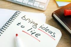 Traiga las ideas a la vida escrita en una nota imagenes de archivo