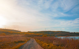 The trail across the field to the right of the sea and the beautiful forest on the horizon, the autumn landscape. Stock Image