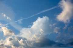 Trail from an airplane in the blue sky with relief clouds. Trail from an airplane in the blue sky with beautiful relief clouds stock photography
