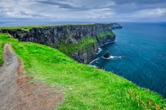 A Trail Along the Cliff's Edge. A trail along the cliff`s edge leading to Hag`s Head, Cliffs of Moher, County Clare, Ireland Stock Photo