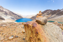Trail cairn duck rocks pile sign mountains lake, travel Bolivia. Royalty Free Stock Photography