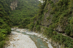 Trail on a cliffside at the Taroko National Park in Taiwan. Lush mountains, river and trail on a cliffside at the Shakadang Trail, Taroko National Park, Taiwan Stock Image