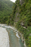 Trail on a cliffside at the Taroko National Park in Taiwan. Lush mountains, river and trail on a cliffside at the Shakadang Trail, Taroko National Park, Taiwan Stock Photo