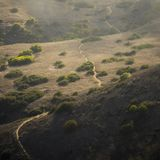 A trail crossing hills with vegetation and light shining through clouds stock photography