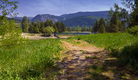 Trail Through Grass Field with Bridge and Mountains Royalty Free Stock Photo