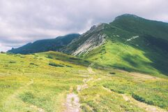 Trail on Green Landscape Over Mountains Royalty Free Stock Image