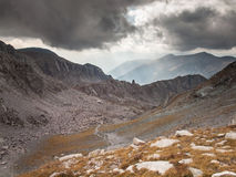 Trail through high mountain landscape with storm clouds and sun Stock Photo