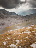 Trail through high mountain landscape with storm clouds and sun Stock Photography