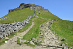 Trail on hill slope under clear blue sky. English countryside landscape, taken along the footpath of the Yorkshire Three Peaks Challenge - grassy slopes Royalty Free Stock Image