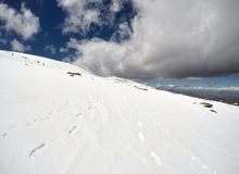 Trail on an icy hillside on a blue day. Trail on an icy hillside on a blue cloudy day stock photo
