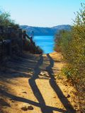 Trail leading to a mountainous lake. The shadows from a wooden railing on a dirt trail leading to a lake with a mountain in the distance. Taken in Southern royalty free stock photography