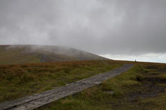 Trail leading two hikers into the mist. The weather in the wicklow way mountains is often wet stock images
