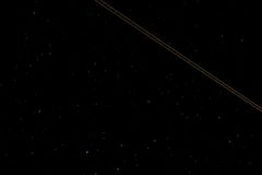 Trail of a light aircraft in the night sky. The starry sky is a trail from the sidelights of the aircraft, long shutter speed Stock Photo