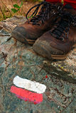 Trail Marker and Boots. Red White Hiking Trail Sign with Walking Boots Royalty Free Stock Image