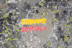 Trail marker for hikers. Red and yellow painted lines indicates the direction of the trail for hikers in the mountains Stock Photography