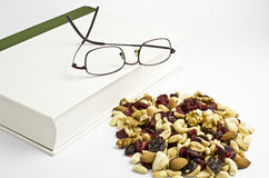 Trail mix, book and eyeglasses Royalty Free Stock Photos