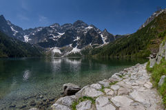 Trail at the mountain lake with rocky summits mirrored in water. Royalty Free Stock Photo
