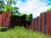 A Trail of Old Red And Black Fence. Fence decaying in an abandoned urban landscape Royalty Free Stock Image